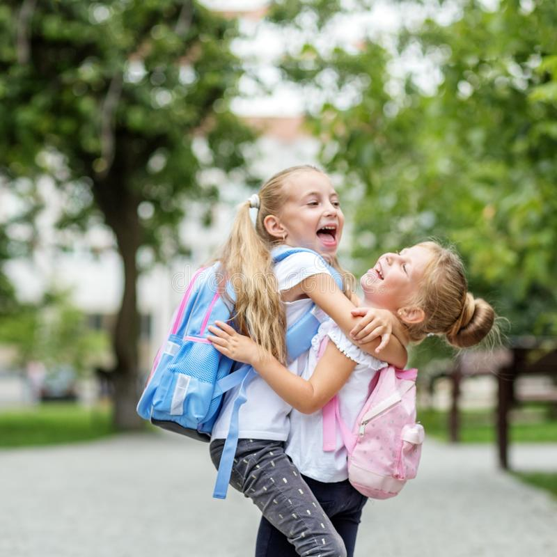 Two children hug and laugh. Square. The concept of school, study, education, friendship, childhood. Two children hug and laugh. Square. The concept of school stock photos
