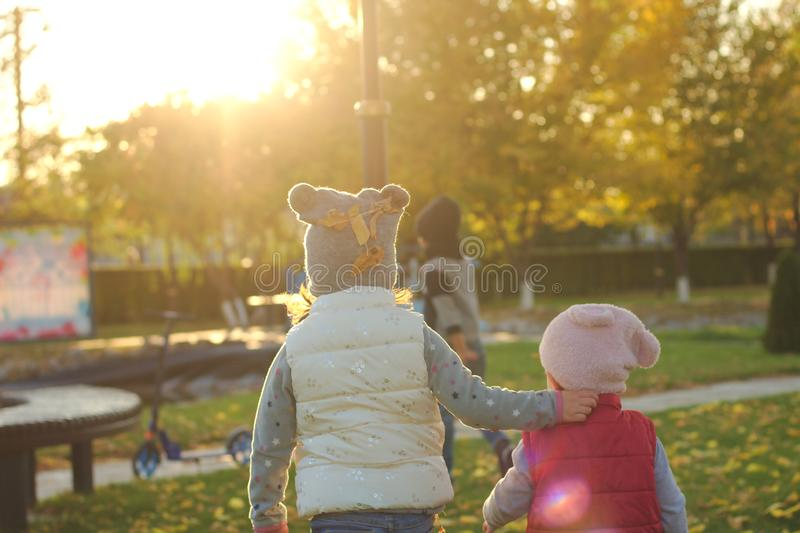Two children hugging on autumn walk in the park outdoors after playing with fallen leaves in the rays of sunset. Positive, adorable, boy, activity, toddler royalty free stock image