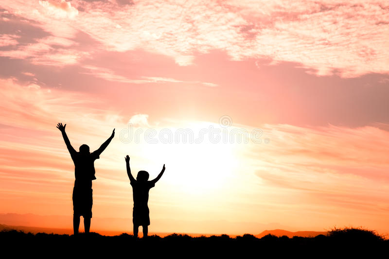 Two children jumping silhouette stock images