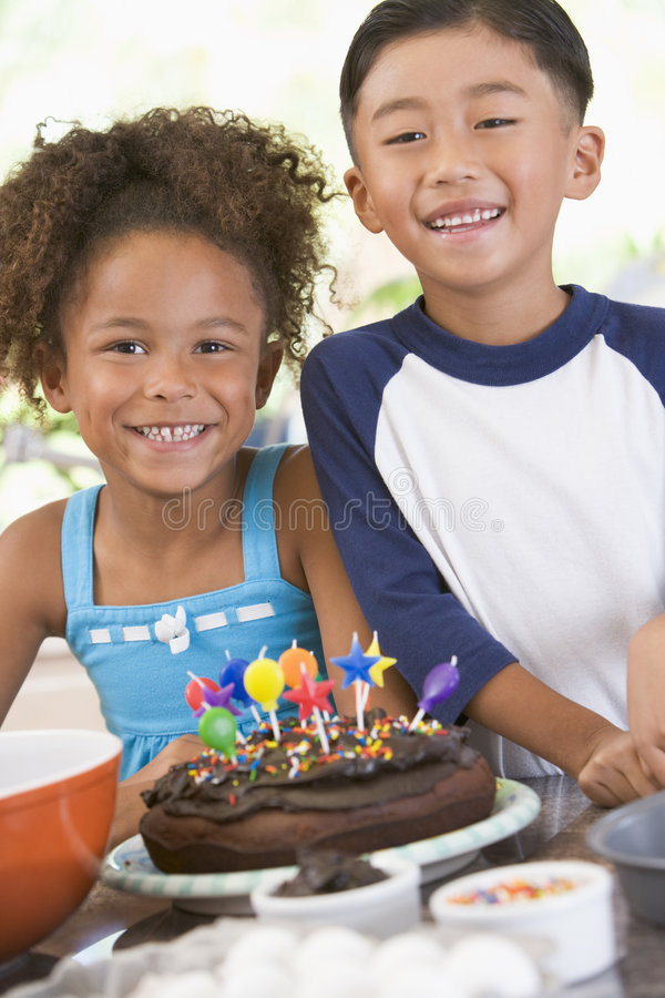 Two children in kitchen with birthday cake. Smiling stock photo