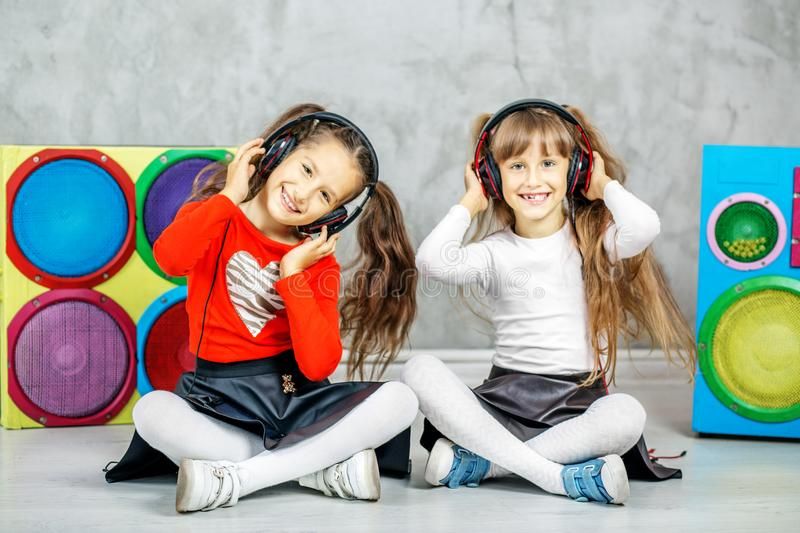 The two children laugh and listen to the songs in the headphones. Concept music, radio, dance, life stroke, rest stock images