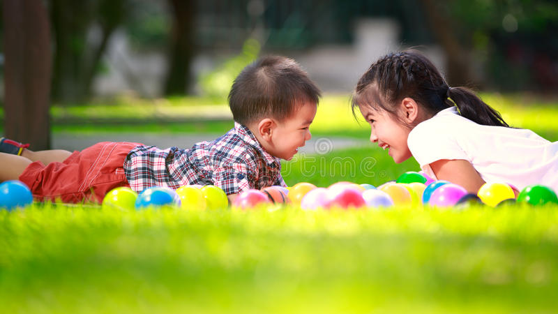 Two children are laying on green grass and smile stock photo