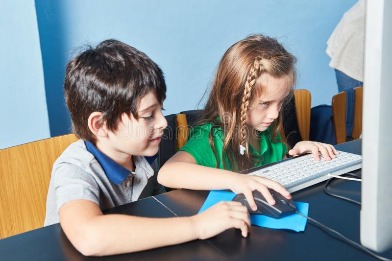 Two children learn concentrated at the computer. In computer science lessons stock photos