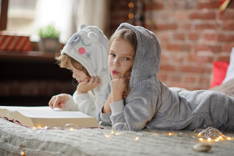 Two children lie on the big bed and read Christmas tales stock photography