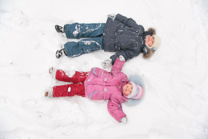 Two Children Lie On Snow Royalty Free Stock Images