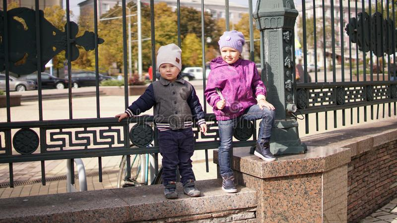 Two children little boy and girl standing at the fence in the park in autumn stock photography