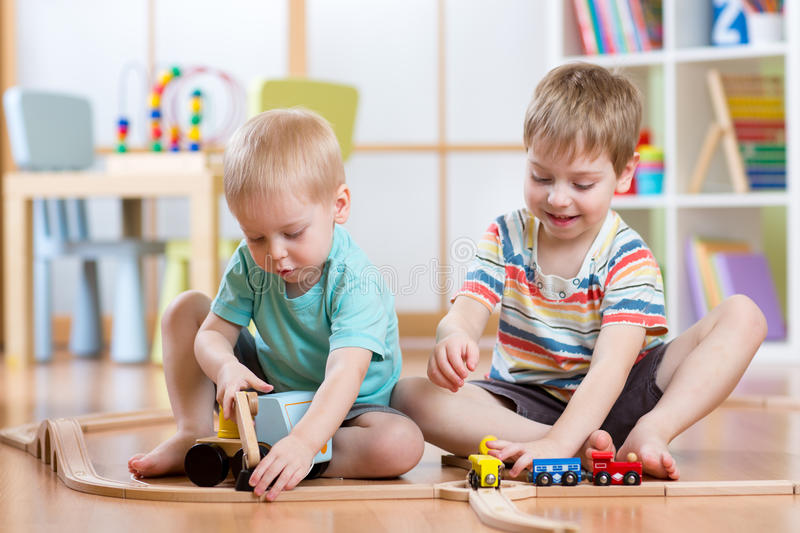 Two children little boys playing role game in daycare. Two cute little boys playing role game in daycare royalty free stock images