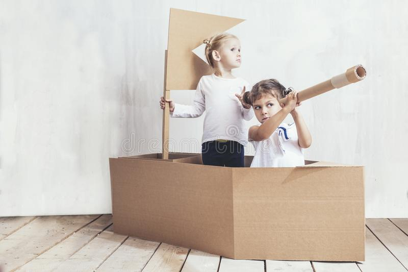 Two children little girls home in a cardboard ship play captains. And sailors royalty free stock images