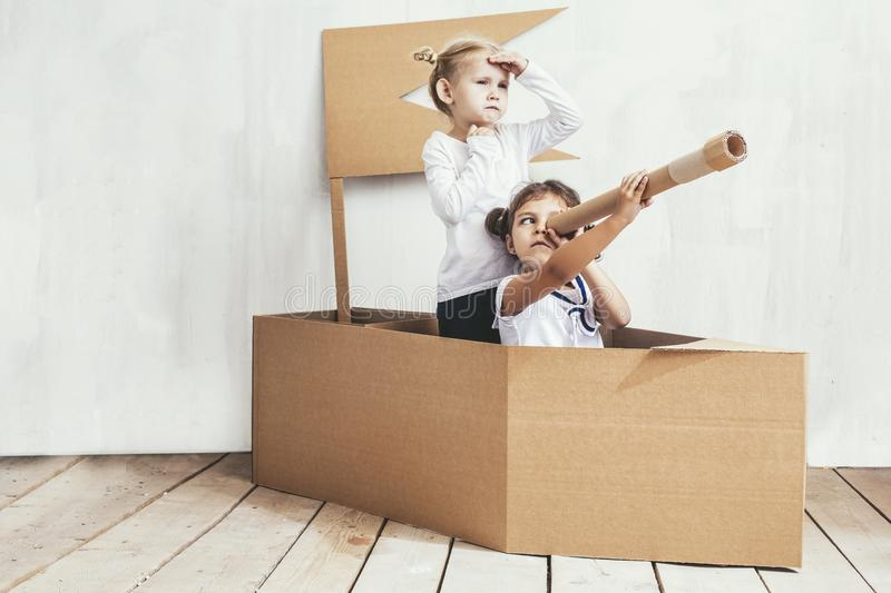 Two children little girls home in a cardboard ship play captains. And sailors stock images