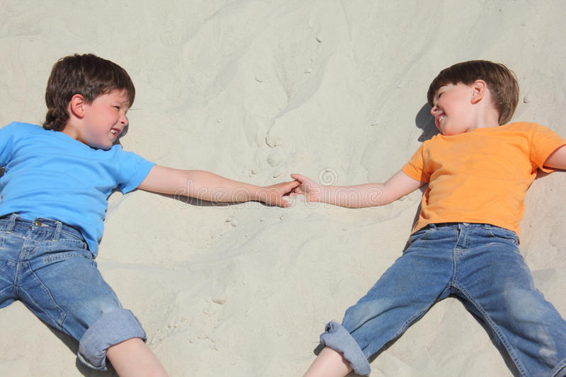 Two children lying nearby on sand royalty free stock photos