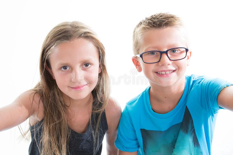 two children make photo selfie with smartphone on white background wall stock image