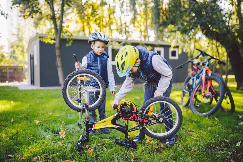 Two children, older boys and younger brother learning repair bike. Two guys siblings in helmets and single clothes use pump tool stock photos