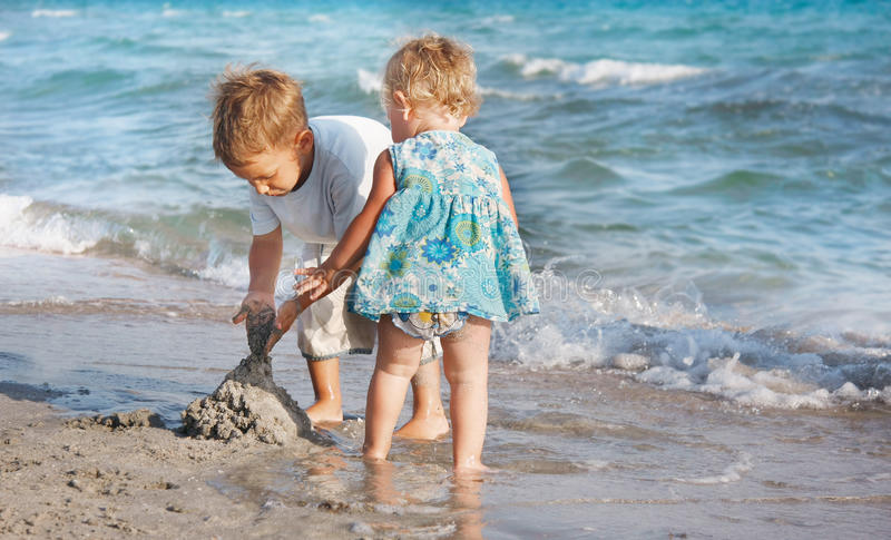 Two children playing on beach. Two children playing on sand beach stock images