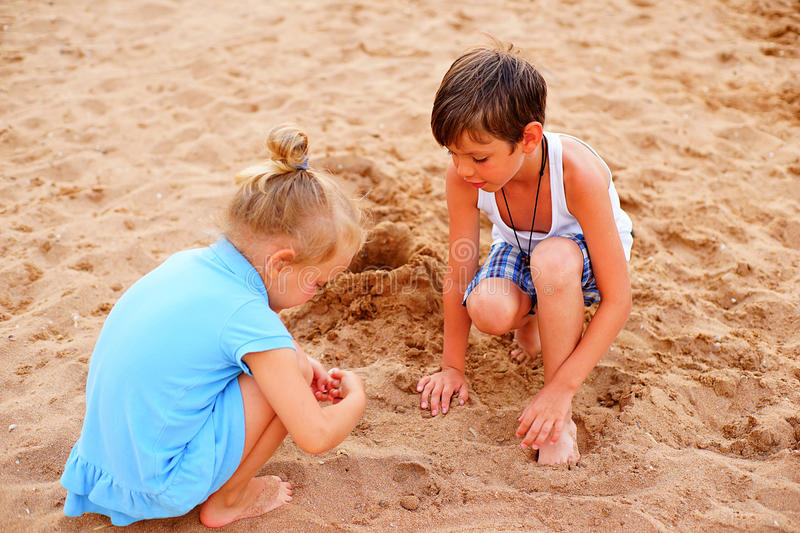 Two children playing on beach. With sand stock photo