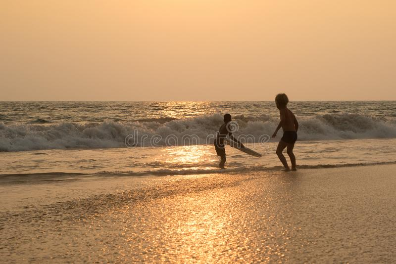 Two children is playing on the beach in sunset. On the ocean royalty free stock images