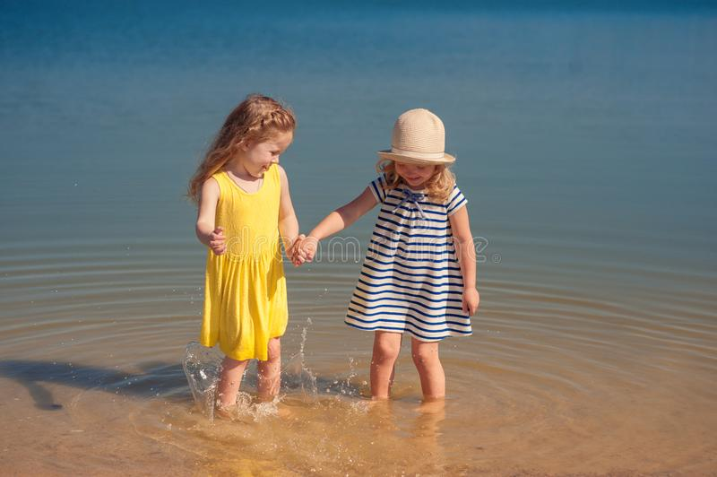 Two children playing on the beach in the water. Splash and laugh stock photography