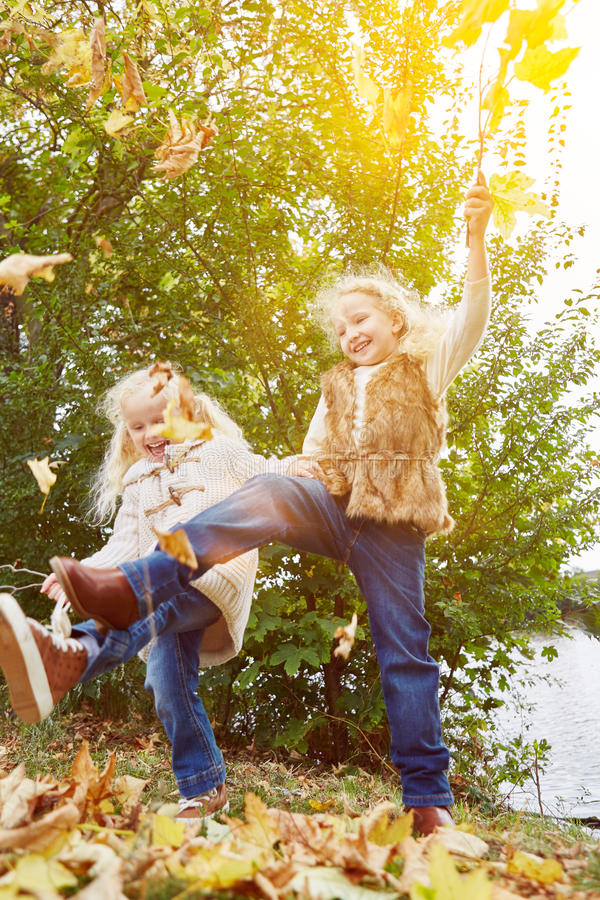 Two children playing and dancing in autumn. With leaves stock photo