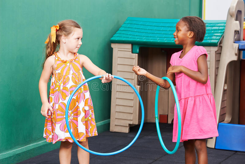 Two children playing with hula hoops stock photography