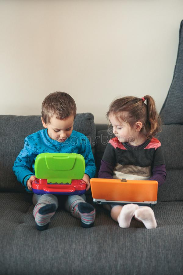 Two children playing with laptops learning basic digits, characters, sounds and images stock photos