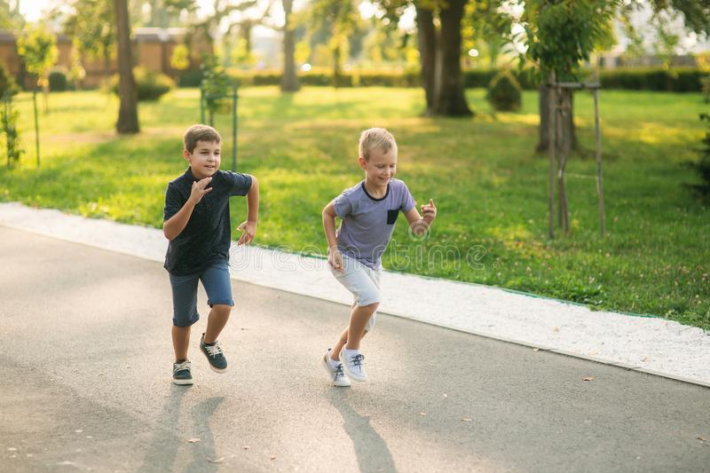 Two children are playing in the park. Two beautiful boys in T-shirts and shorts have fun smiling. They eat ice cream. Jump, run. Summer is sunny stock photo
