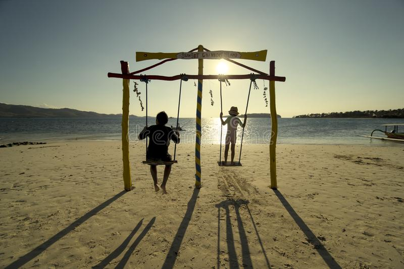 Two children playing with swing on the beach stock images