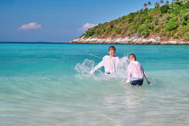 Two children playing in tropical sea. Kids playing In ocean surf on vacation. Cute boys splashing water on each other. Sunny day. royalty free stock photography