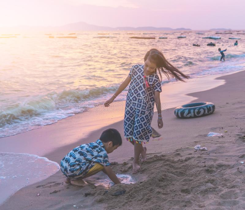 Two children is playing with wave and sand in Pattaya Beach Thailand stock image