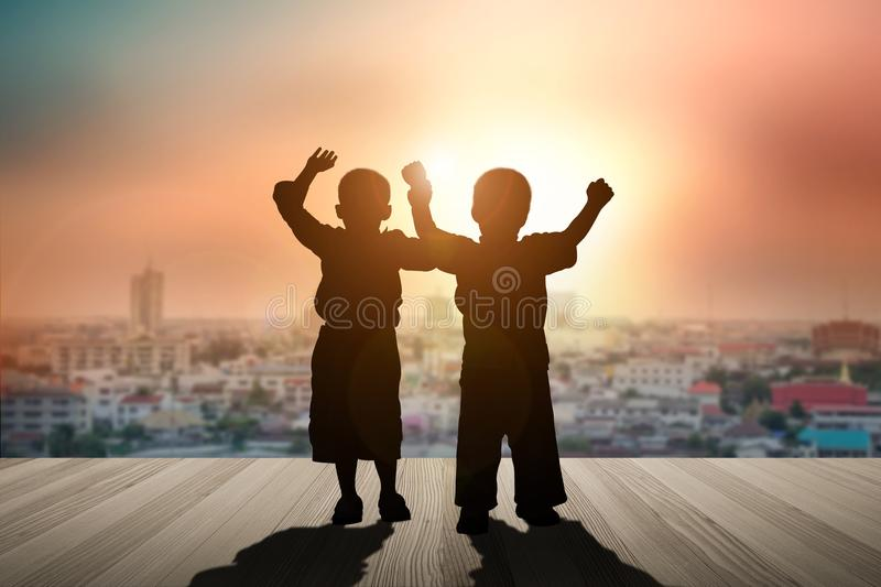 Two children raise their hands on a wooden balcony in the city. stock photo
