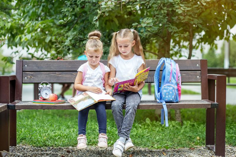 Two children read books in the school park. The concept of school, study, education, friendship, childhood.  stock images