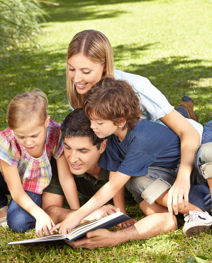Two children reading book with family stock images