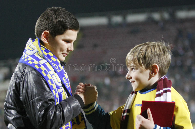 Rapid Bucharest - Petrolul Ploiesti. Two children, representing the two teams, change the flags of the teams, representing the idea of fair-play, at the royalty free stock images
