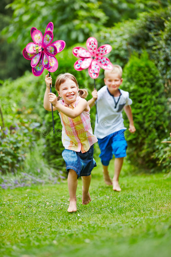Two children running in garden in summer. Two happy children running in garden in summer with windmills royalty free stock images