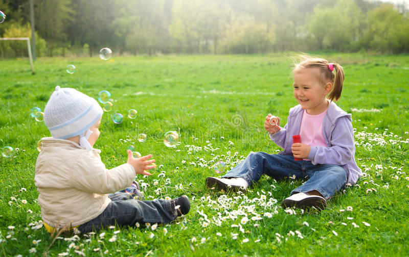 Two Children Are Sitting On Green Meadow Royalty Free Stock Photo