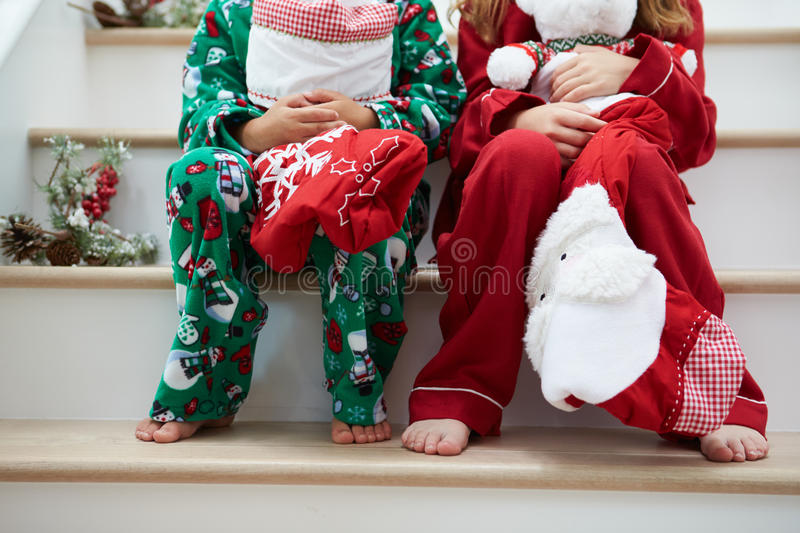 Two Children Sitting On Stairs With Christmas Stockings ...