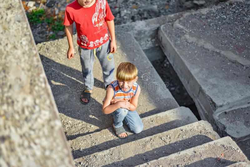 Two children are sitting on the steps of an abandoned building, a concept of the life of street children orphans royalty free stock image
