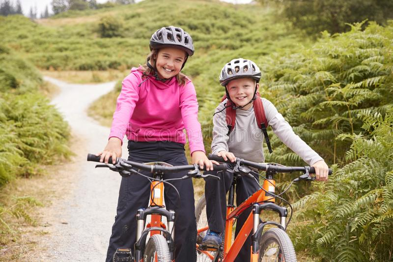 Two children sitting on their mountain bikes on a country path laughing, front view stock images