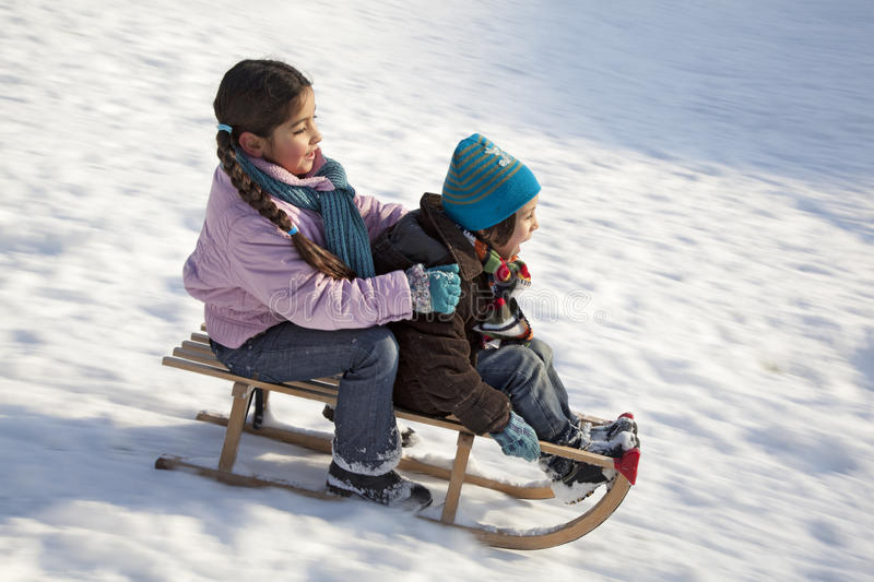 Two children on a sled having fun. In the snow stock photos
