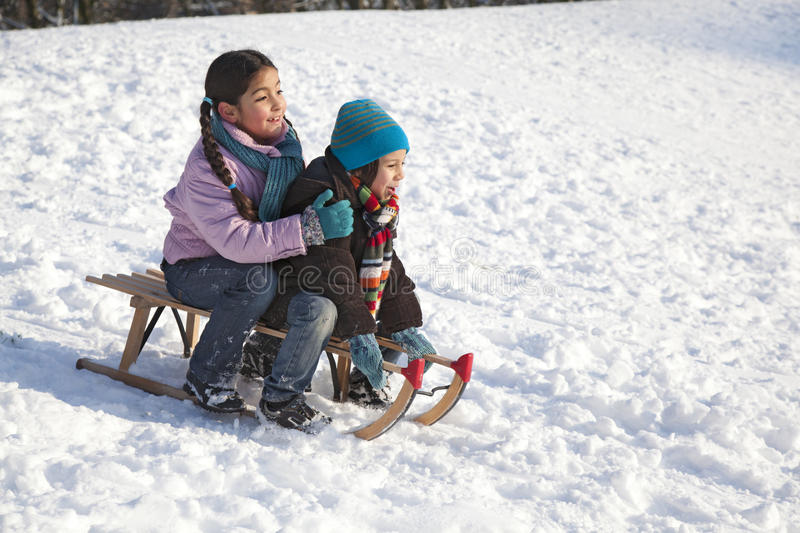 Two children on a sled having fun. In the snow royalty free stock photos