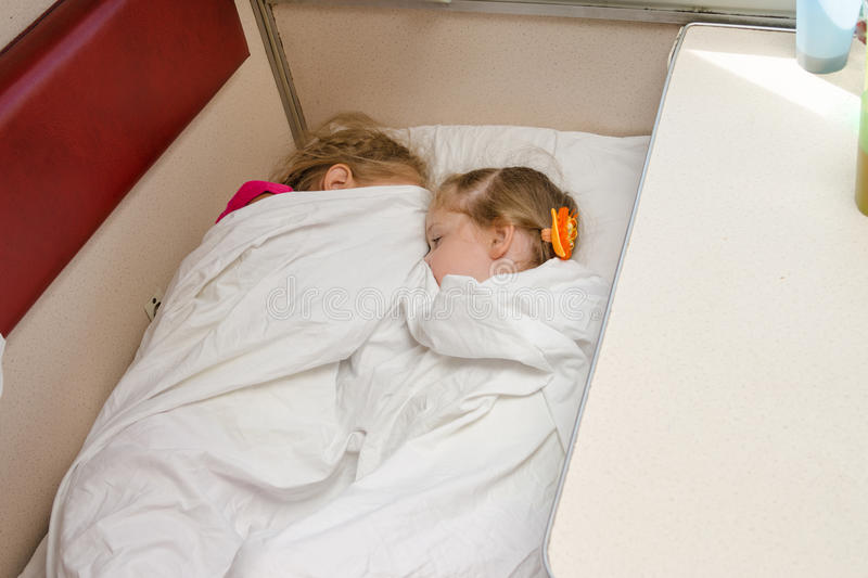 Two children sleep on train on the same ground location in the second-class compartment wagon. Two children sleep on the train on the same ground location in the stock photos