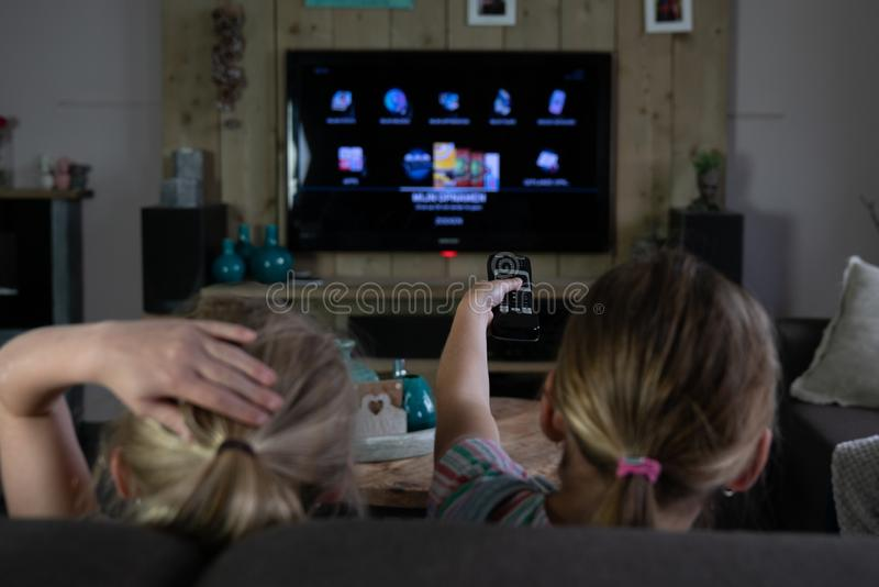 Two children sliding through the apps on a smart tv. back of the children with the focus on the remote control stock photo