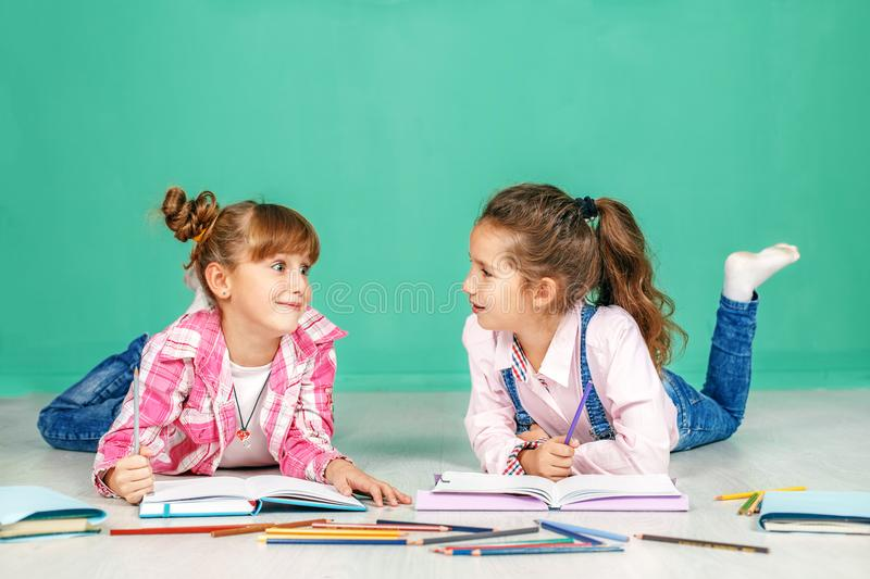 Two children speak and teach homework. The concept of childhood, learning, friendship, family, school, lifestyle. stock image