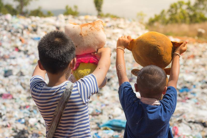 Two children stand holding dolls collected from garbage dumps.the lives and lifestyles of the poor, The concept of child labor stock images