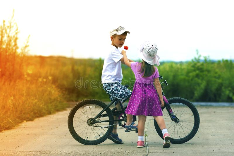 Two children in summer day bicycle and flower boy and girl.  stock images
