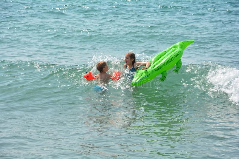 Two children swim in the sea with crocodile - air bed royalty free stock photos