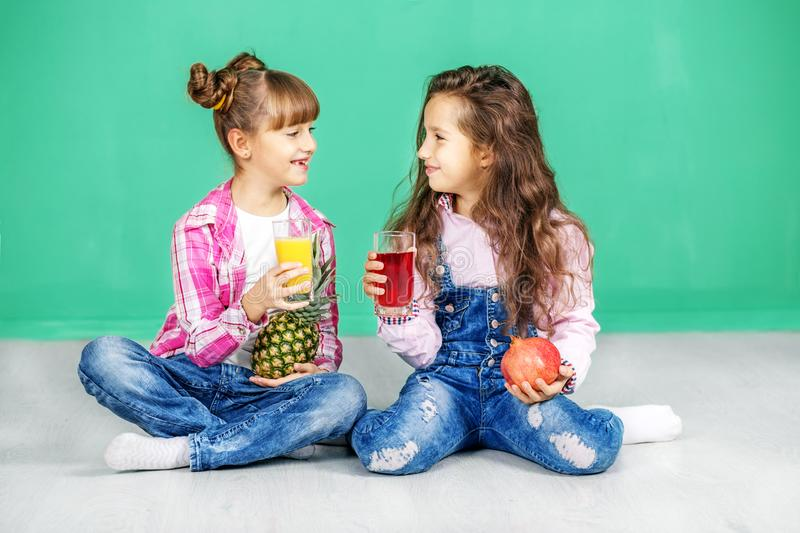 Two children are talking and drinking juice. Girls with pineapple and pomegranate. The concept of a healthy royalty free stock images