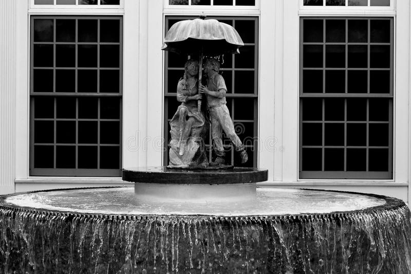 Two Children Under Umbrella Fountain. A statue of two children under an umbrella with a fountain in the historic town of Greendale, WI royalty free stock image