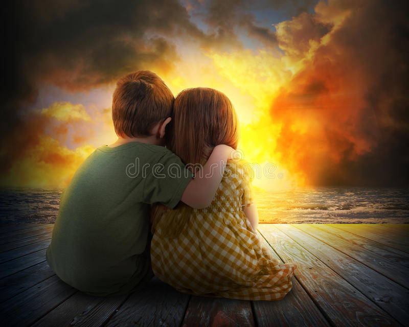 Two Children Watching Summer Sunset. A little boy and girl are hugging and watching the sunset in the sky. The children are sitting on wood for a family, love or stock image