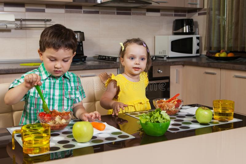 Download Two Children Who Eat Healthy Food In The Kitchen Stock Photos - Image: 31678133