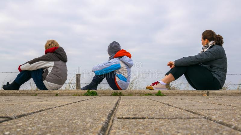 Two children and a woman who sit down on the pavilions and watch the North Sea, from the Netherlands, dressed thick with blue sky stock photos