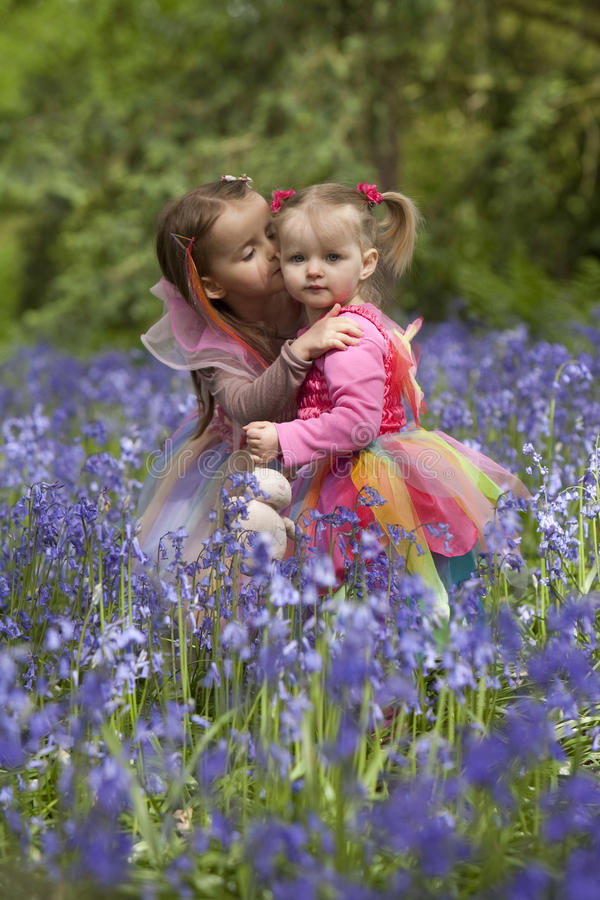 Two children in a wood filled with spring bluebells stock images